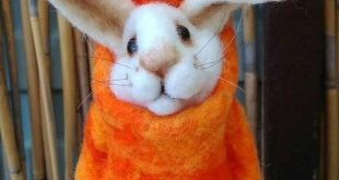 Funny bunny in carrot, rabbit soft sculpture. Easter decorations